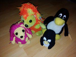 Vier Plüschtiere, sitzen auf dem Boden. Zwei Igel und zwei Pinguine.