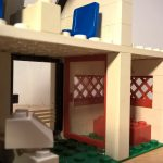 """Eine Polizeidienststelle aus LEGO® von hinten gesehen.. Detailansicht der """"Wartezone"""" einer art Zelle mit Glastür"""