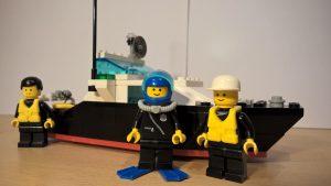 Ein Polizeiboot aus LEGO®, da vor stehen drei Polizisten, zwei mit Schwimmweste, einer mit Taucheranzug.