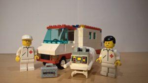 Zwei angehörige des Rettungsdienstes stehen mit ihrer Ausrüstung vor ihrem RTW