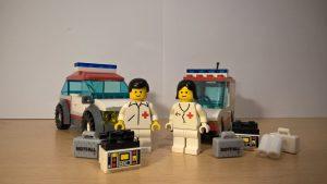Zwei Fahrzeuge, mit einem Sanitäter und einer Ärztin. Die beiden stehen vor ihren Einsatzwagen. Vor ihnen liegt ihre Ausrüstung