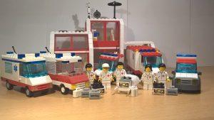 LEGO® Rettungsdiensteinheiten stehen mit ihren Fahrzeugen und Ausrüstung vor dem Krankenhaus